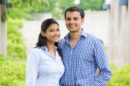 indians: Closeup portrait, attractive wealthy successful couple in blue shirt and striped outfit holding each other smiling, isolated outside green trees background.