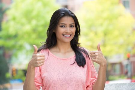 actitud: Primer retrato de mujer joven y bonita en camisa de color rosa con dos pulgares para arriba signo gesto aislado al aire libre de fondo. Emoción positiva expresión facial sentimientos, signos y símbolos, el lenguaje corporal