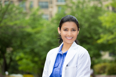 Closeup headshot portrait of friendly, cheerful, smiling confident female, healthcare professional with lab coat. isolated outdoors outside green trees background. Patient visit. Stock Photo