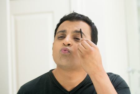 narcissism: Closeup portrait, young handsome egotistical man in black t-shirt looking at mirror showing kisses and duck face, combing eyebrows admiring his appearance inside indoors background Stock Photo