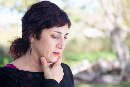 low: Closeup portrait of philosophical thinking dark hair woman hand on chin, deep in thought, isolated outside outdoors background. Human emotions, expression, reaction