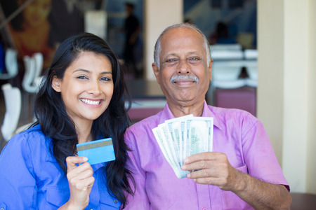 mature mexican: Closeup portrait rich elderly gentleman in pink shirt and lady in blue top holding greenbacks and credit card. Booming economy concept, buy, sell, award. Make money at home