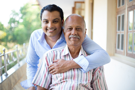 indians: Closeup portrait, family, young man in blue shirt holding older man in striped shirt from behind, happy isolated on outdoors outside balcony background