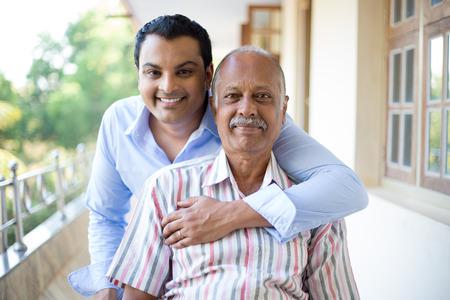 rodzina: Portret z bliska, rodzina, młody mężczyzna w niebieskiej koszuli gospodarstwa starszy mężczyzna w koszuli w paski z tyłu, szczęśliwy na zewnątrz balkon tle