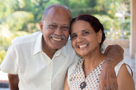 indian people: Closeup portrait, retired couple in white shirt and dress holding each other smiling,enjoying life together, isolated outside green trees background. Stock Photo