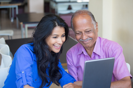 Closeup portrait, sitting young woman showing elderly to use laptop, watching good movie, isolated indoors background