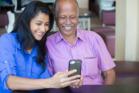 citizens: Closeup portrait elderly gentleman in pink shirt and lady in blue top family enjoying mobile phone fun, isolated indoors background