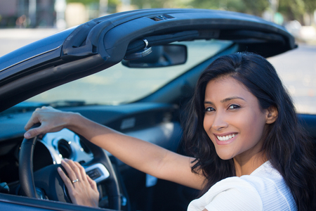 new car: Closeup portrait young smiling, happy, attractive woman smiling from behind in her brand new sports car drop top, hand on steering wheel, isolated outdoors background