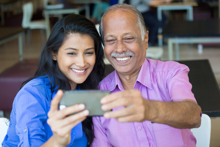 father daughter: Closeup portrait happy elderly gentleman in pink shirt and lady in blue top taking selfie together, isolated indoors background. Say cheese and smile Stock Photo