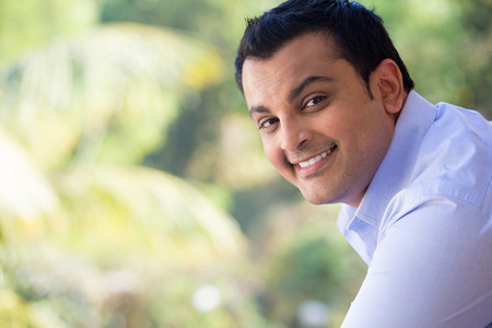 indians: Closeup portrait of handsome happy young man in blue shirt standing outside on his balcony, isolated outdoors outside background with green trees