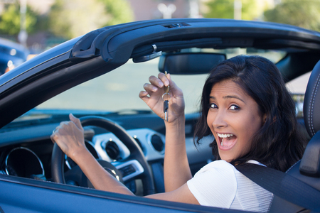 rent: Closeup portrait, young cheerful, joyful, smiling, gorgeous woman holding up keys to her first new sports car. Customer satisfaction