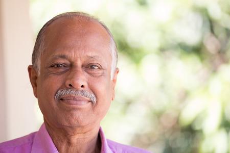 abuelo: Retrato del primer tiro en la cabeza del anciano en camisa de color rosa, el contenido, el fondo al aire libre exterior aislado con los árboles de sol verdes Foto de archivo