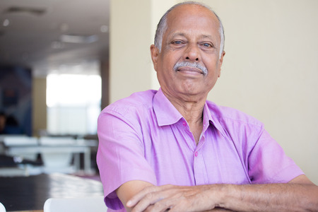 Closeup headshot portrait of elderly gentleman arms crossed folded, in pink shirt smiling, content, isolated sitting indoors background Foto de archivo