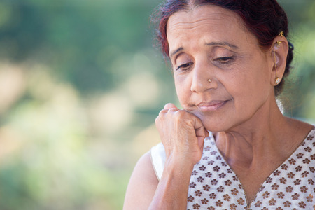 senior female: Closeup portrait, morose elderly lady, downcast gloomy, resting face on hand, isolated green outdoors background Stock Photo