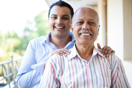 abuelo: Primer retrato, familia, hombre joven en camisa azul que sostiene el hombre de más edad en camisa a rayas de detrás, feliz aislado en outdoors fondo balcón