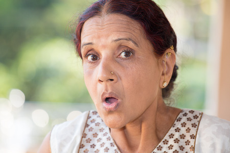 mature mexican: Closeup portrait, elderly woman in white dress taken aback, blown away, by what she sees or hears, isolated outdoors outside background with green trees Stock Photo