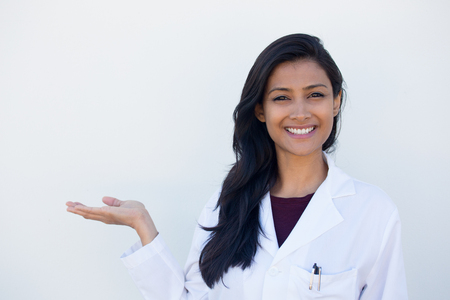 Closeup portrait of friendly, smiling confident female doctor advertising copy space, healthcare professional isolated white background. Positive human face expression, emotion attitude