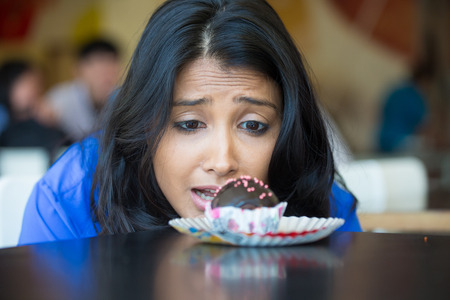 good food: Closeup portrait of desperate woman in blue shirt craving fudge with pink sprinkles dessert, eager to eat, isolated indoors background