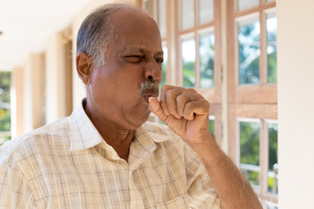 coughing: Closeup portrait, old man coughing with post nasal drip bug, really sick in bad weather, holding fist to mouth, isolated outdoors outside background Stock Photo