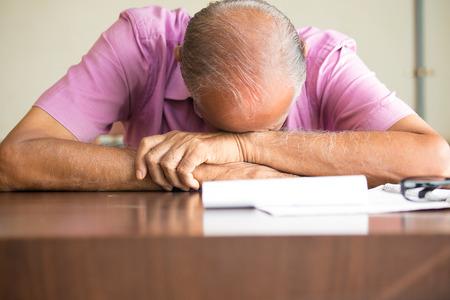 hombres maduros: Retrato del primer, viejo y cansado para dormir jefe calva después de llenar tanto papeleo, que descansa sobre el escritorio, aislados en el interior de fondo. Agotadoras horas de trabajo, necesitará más cafeína