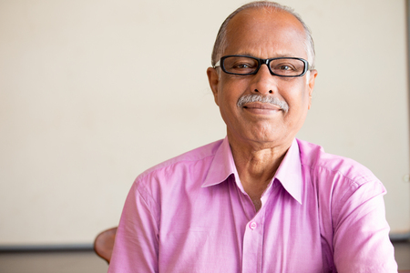 indian business man: Closeup portrait, smart elderly man in pink shirt with dark eye glasses, specs, sitting down, isolated indoors white chalkboard background