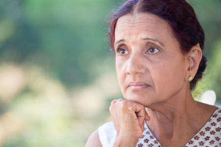 mature mexican: Closeup portrait, morose elderly lady, daydreaming about the future looking ahead, resting face on hand, isolated green trees outdoors background