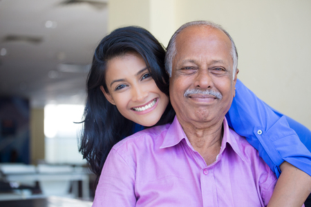 asian old man: Closeup portrait, family, young woman in blue shirt holding older man in pink collar button down from behind, happy isolated indoors home background