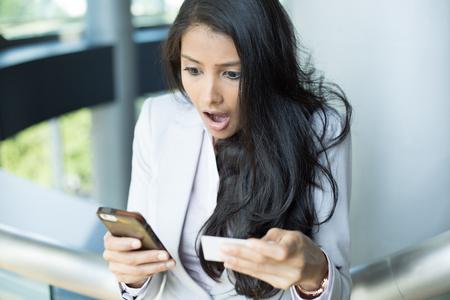 Close-up portret, jonge vrouw in het wit grijs pak op zoek naar mobiele telefoon en papier, geschokt door wat ze ziet, geïsoleerde achtergrond binnen. Lot uit de loterij
