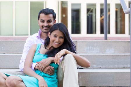 Closeup portrait, attractive wealthy successful couple in pink shirt and green dress holding each other smiling, isolated outside stairwell background. Stock Photo