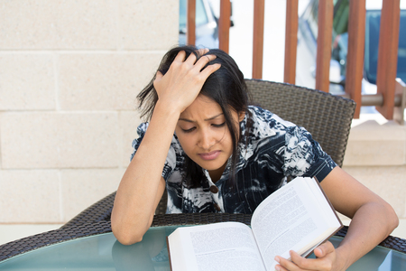 Closeup portrait, woman frustrated by what she has to read for school, hand on head, tight deadline for studying, isolated outdoors outside background. Negative emotions facial expressions