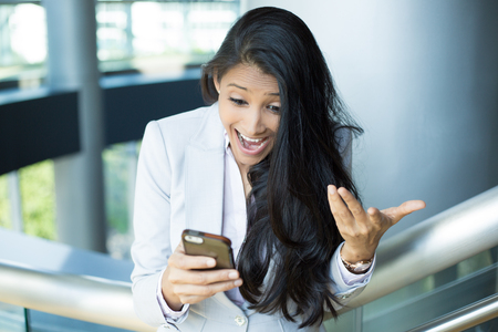 Closeup portrait of pretty young woman looking shocked, open mouth and eyes, cell phone watching sports game match or reading an sms, e-mail, viewing latest news, isolated indoors office background 免版税图像