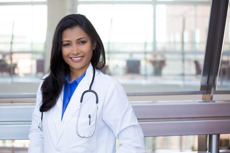 doktor: Zbliżenie portret headshot przyjazny, wesoły, uśmiechnięty pewni kobieta, medyczny z fartuchu. odizolowanych pomieszczeniach biurowych tła kliniki. Wizyta pacjenta.