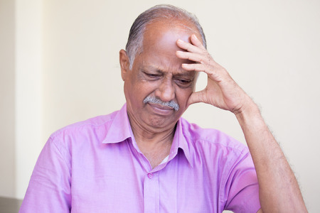 Closeup portrait, morose elderly pensioner, downcast gloomy, resting hand on head, isolated indoors home background. Negative emotion facial expressions