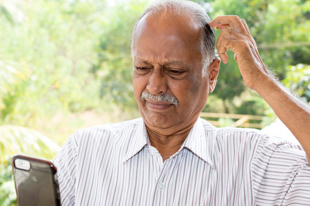 Closeup portrait, gentleman with mustache in white striped shirt, dumbfounded flabbergasted by what he sees on cell phone, isolated outside outdoors office background Stockfoto