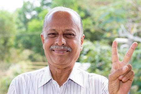 Retrato del primer, señor de edad alegre en camisa de rayas blancas que soporta dos dedos, aislado fuera al aire libre fondo