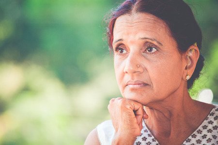 Closeup portrait, morose elderly lady, daydreaming about the future looking ahead, resting face on hand, isolated green trees outdoors background