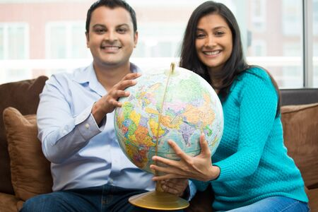 embark: Closeup portrait young couple holding map globe showing excitement to travel the world, isolated indoors home background Stock Photo