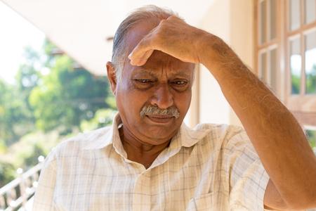 désolé: portrait Gros plan, retraité âgé morose, la main reposant sombre abattu sur la tête, isolé à l'extérieur à l'extérieur du milieu familial Banque d'images