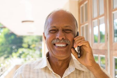 likeable: Closeup portrait, happy bald pensioner enjoying phone conversation. Call me on my cell phone, isolated outdoors outside background
