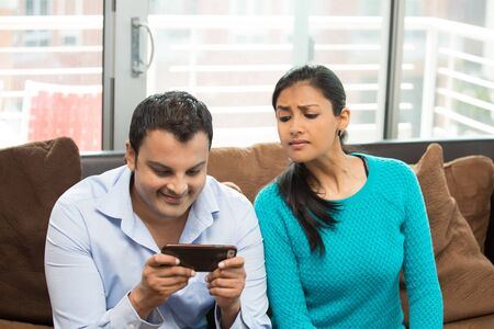 sneaky: Closeup portrait, woman looking sneaky at man texting in secret, isolated home house indoors background