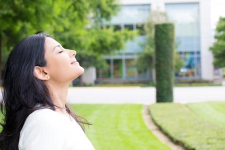Retrato del primer, mujer joven en camisa blanca de respiración en el aire quebradizo fresco después de largo día de trabajo, aislado de fondo al aire libre exterior. Parar y oler las rosas, conectarse con la naturaleza