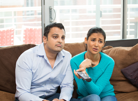 they are watching: Closeup portrait, couple sitting on brown leather couch, watching TV, holding remote, sad by what they see, isolated indoors flat background.