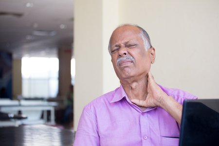 senior man on a neck pain: Closeup portrait, elderly gentleman in pink shirt with cramping neck pain after using black laptop all day, trying to soothe with hand, isolated indoors background