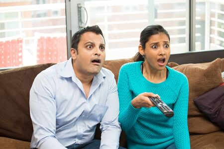 they are watching: Closeup portrait,couple sitting on brown leather couch, watching TV, holding remote, surprised at what they see, jaw drop, isolated indoors flat background Stock Photo