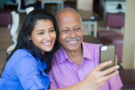 mature mexican: Closeup portrait happy elderly gentleman in pink shirt and lady in blue top taking selfie together, isolated indoors background. Say cheese and smile Stock Photo