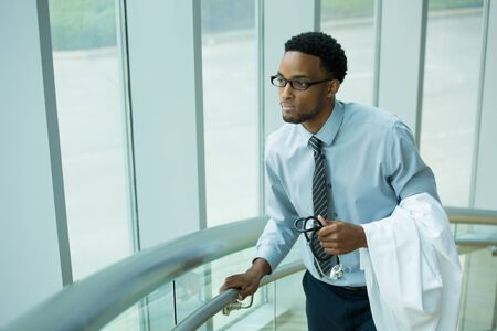 residents: Closeup portrait, young healthcare professional, walking up stairs with lab coat on arm, daydreaming looking outside, isolated indoors hospital clinic background