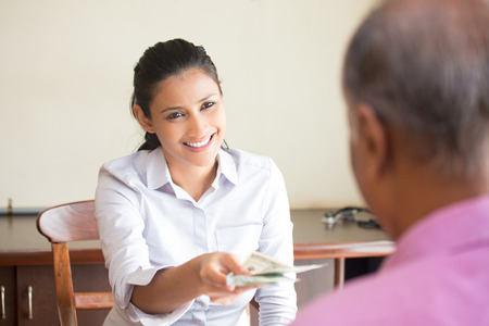 excellent: Closeup portrait, woman giving cash back refund, isolated indoors office background.  Excellent customer service with a smile