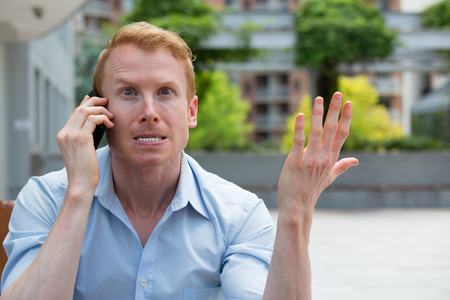 portrait Gros plan, jeune homme ennuyé, frustré, énervé par quelqu'un parler sur son téléphone mobile, les mauvaises nouvelles, à l'extérieur isolés fond à l'extérieur. longs temps d'attente, les conversations horribles notion