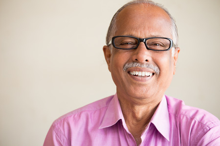 Closeup portrait, smart elderly man in pink shirt with dark eye glasses, specs, sitting down laughing, isolated indoors white chalkboard background Standard-Bild