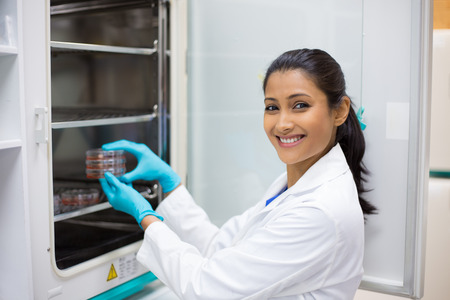 culture: Closeup portrait, young lab researcher holding tissue culture dishes in incubator. Isolated lab background